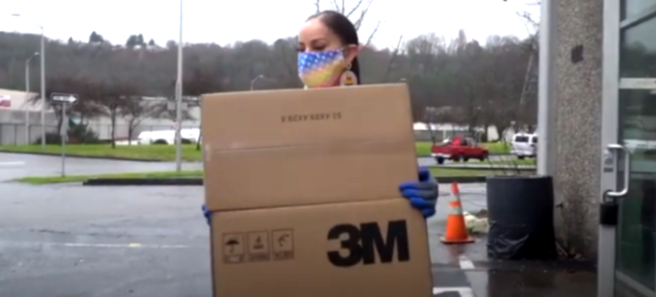 woman of color wearing face covering carries boxes of ppe